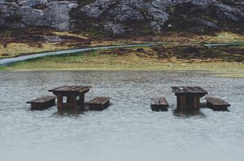 Two picnic benches sitting in a heavily flooded park