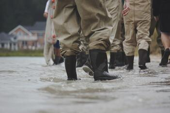 A group of people wade through a flooded street in rain boots