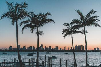 An image of the Miami skyline across a body of water during sunset
