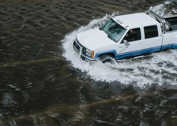 A truck attempts to drive through water after recent flooding in Fort Lauderdale