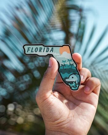 A small, stylized sticker of the state of Florida, cut out in it's shape