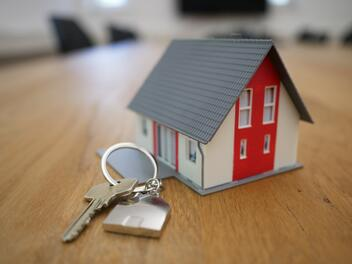 A small, keychain sized house, representing property