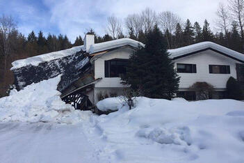 A house with a collapsed roof, completely covered in snow after a winter storm