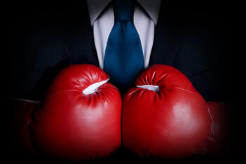 A man in a suit wears boxing gloves, prepared to fight his insurance company