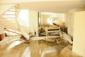 A homeowner has stacked furniture to limit damage after a flood.