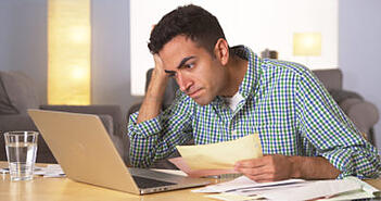 A frustrated man sitting at his laptop with a handful of denied insurance paperwork
