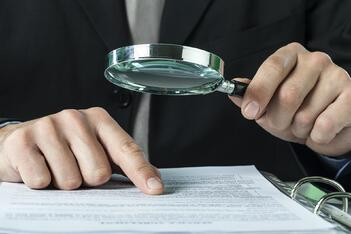A man looks over insurance documents with a magnifying glass