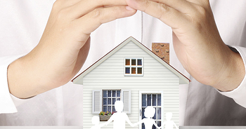 A pair of hands cup a small model home, signifying the protection of home insurance