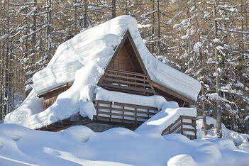 A home is covered with dangerous amounts of snow and ice.