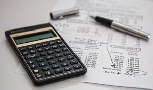 A calculator and documents, processing student debt and buying a home