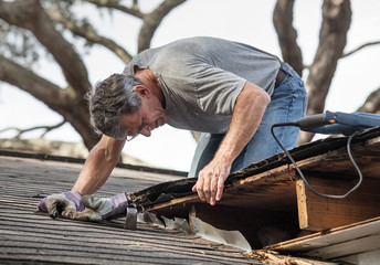 A man on a roof struggles to repair a roof leak from water damage
