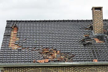 The tiles of a roof are damaged from a recent storm