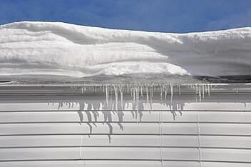 A roof is weighed down by excess snow and ice