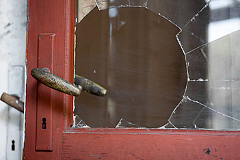 A smashed window next to a door handle, indicating a robbery