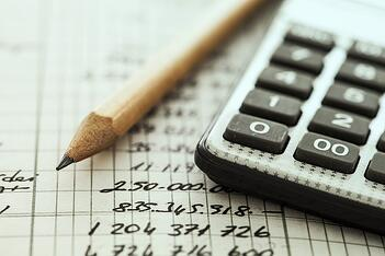 A pencil and calculator documenting expenses