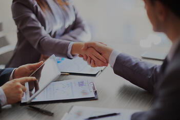 Two people shake hands across the table in mutual agreement.