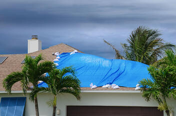 A storm damaged home in Jupiter with a tarp on the roof