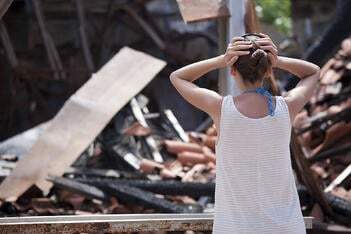 A woman looks on in shock after her property is destroyed