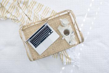 A laptop and coffee sitting on a kitchen island, used to run a home business