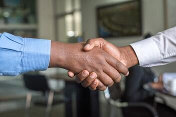 A close up shot of two men shaking hands at the conclusion of a deal