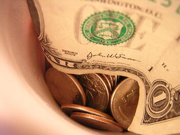 A cup full of coins and single dollar bills, representing the better return you could receive if you reopen your claim