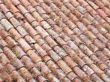 Heavily damaged clay roof tiles after a hurricane