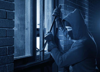 A burglar makes his entrance into a home that is about to be robbed.